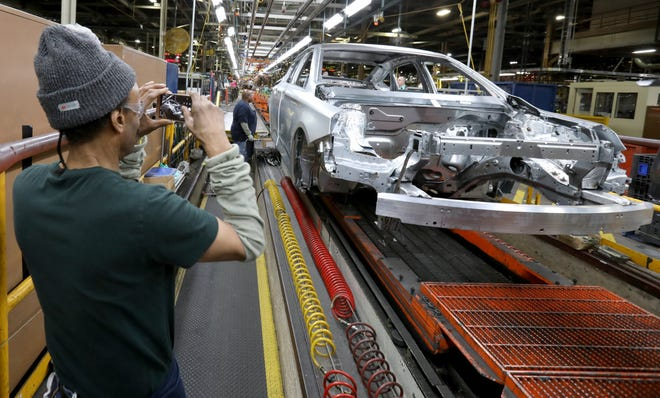 Gregory Edwards, 64, of Detroit takes pictures of the very last 2020 Chevrolet Impala that was making its way down the production line on Feb. 20 inside the GM Detroit-Hamtramck Assembly plant. The plant is being retooled and fitted for electric vehicles.
