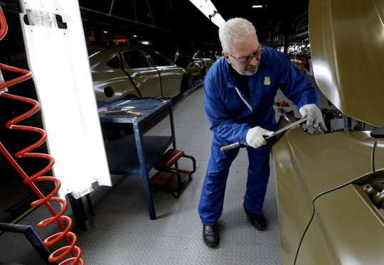 Joe Nickowski, 62, of Taylor works at getting a small bump out of a 2020 Chevrolet Impala before it would be sent for final paint on Thursday inside the GM Detroit-Hamtramck Assembly plant. The car was nearing its end of production as the plant is being retooled and fitted for electric vehicles.