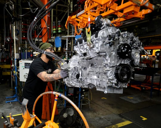 General Motors temporary worker Anthony Madkin of Detroit moves an engine and transmission of a 2020 Chevrolet Impala on a hoist to another production line on Tuesday, February 18, 2020 inside the GM Detroit-Hamtramck Assembly plant. 