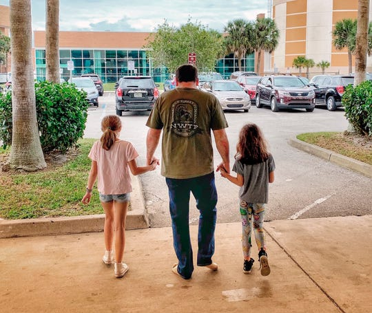 This photo provided by Roush Racing shows NASCAR driver Ryan Newman and his daughters, Brooklyn Sage, left, and Ashlyn Olivia, leaving Halifax Medical Center on  Wednesday.