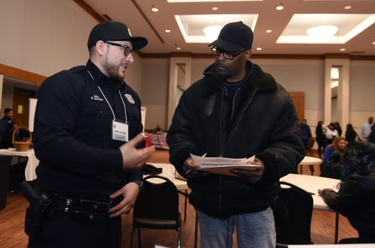 DPD officer Elpidio Sancen, (l), of the recruiting departmement, talks to Idrissa Reed,47, of Detroit about becoming a police officer and the requirements that he has to meet.