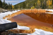 In this Oct. 12, 2018 file photo, water contaminated with arsenic, lead and zinc flows from a pipe out of the Lee Mountain mine and into a holding pond near Rimini, Mont. The community is part of the Upper Tenmile Creek Superfund site, where dozens of abandoned mines have left water supplies polluted and residents must use bottled water.