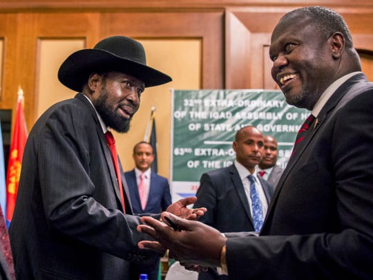 FILE - In this Thursday, June 21, 2018 file photo, South Sudan's President Salva Kiir, left, and opposition leader Riek Machar shake hands during peace talks in Addis Ababa, Ethiopia.