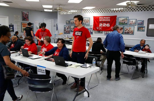 Volunteers help check people in to vote early at the Culinary Workers union Monday, Feb. 17, 2020, in Las Vegas.
