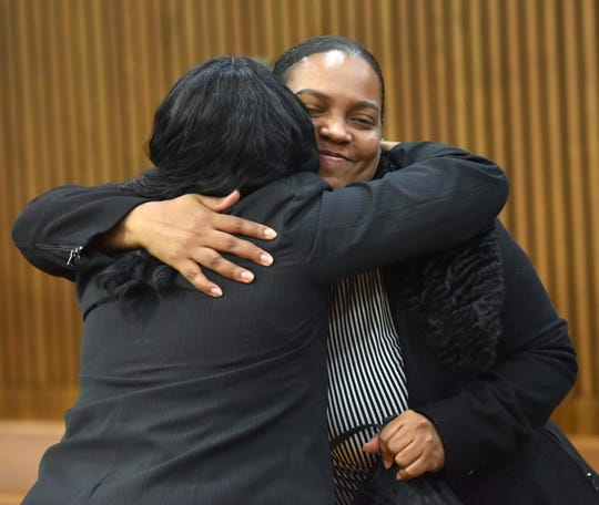 Ramon Ward's sister, Elise Moore, right, hugs a member of the prosecutor's conviction integrity unit.
