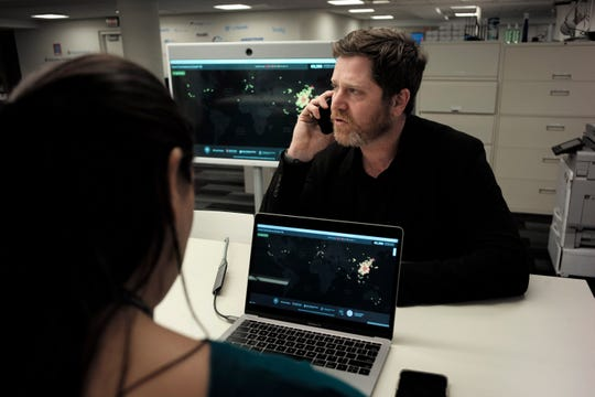 In this Thursday, Feb. 13, 2020 photo, John Brownstein, right, co-founder of HealthMap, a system using artificial intelligence to monitor global disease outbreaks, speaks on a phone in a HealthMap work area at Boston Children's Hospital in Boston.
