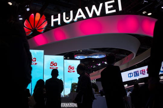 FILE - In this Oct. 31, 2019, file photo, attendees walk past a display for 5G services from Chinese technology firm Huawei at the PT Expo in Beijing.