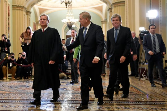 Supreme Court Chief Justice John Roberts, left, walks with Sen. Lindsey Graham from the Senate Chamber on Capitol Hill in Washington, Wednesday, Feb. 5, 2020