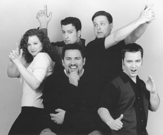 This 2000 promotional photo shows former cast member Sara Fouracre, Mojo (center) and Spike in the front row, along with other cast members of the Mojo in the Morning radio show.