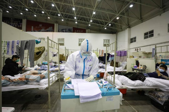 A medical staff member works near COVID-19 patients recuperating in a temporary hospital converted from an exhibition center in Wuhan on Wednesday.