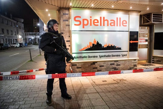 A police officer stands guard in front of a gambling hall near the scene after a shooting in central Hanau, Germany Thursday, Feb. 20, 2020. Eight people were killed in shootings in the German city of Hanau on Wednesday evening, authorities said.