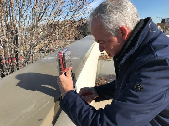 Jim Haselmaier, co-creator of Train Alert, adjusts a camera mounted on the roof the Schraders building in north Fort Collins. The Train Alert system automatically detects train traffic on the BNSF Railway line and sends out notices and predicted arrival times at various intersections.