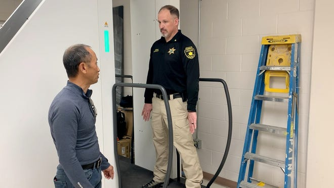 Cascade County Sheriff Jesse Slaughter (right) and KPrime CEO Kham Lin demonstrates the SPECTRUM BODYSCAN DV at the Cascade County Regional Detention Center on Thursday, Feb. 19, 2020.