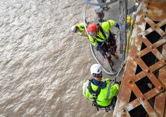 High above the flood swollen Ohio River, bridge inspectors with the Kentucky Transportation Cabinet prepare to rappel off one of the bridge piers on the northbound U.S. 41 Twin Bridge Thursday morning, after the Coast Guard reported a barge hit on the center pier Tuesday night.