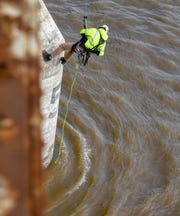 A bridge inspector with the Kentucky Transportation Cabinet rappels down for a close look at one of the bridge piers on the northbound U.S. 41 Twin Bridge Thursday morning, after the Coast Guard reported a barge hit on the center pier Tuesday night.