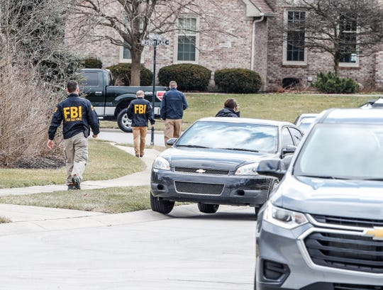FBI and other law enforcement officials leave the scene of a raid at a home located on Mansfield Place, in the Huntington Chase neighborhood of Carmel, Ind., on Thursday, Feb. 20, 2020.