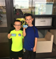 "Proudly showing off their library cards, the Barr's sons, John-Adam and Nate often help their parents with ideas and suggestions.  ""We couldn't do this without them,"" said mom Betsy Barr."
