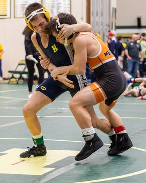 Hartland's Patrick Wlodyga (left) won two matches by pins in less than 50 seconds in the team wrestling regional at Walled Lake Western.