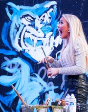 Speed painter Jessica Haas reveals her Tiger-themed creation for the crowd during halftime in the Memphis Tigers vs. East Carolina Pirates game at the FedExForum on Wednesday, Feb. 19, 2020.