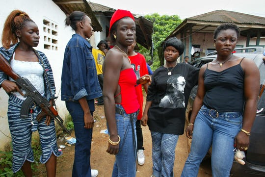 2003: Black Diamond, center in red, a leader of Liberians United for Reconciliation and Democracy (LURD) fighters, poses with other women soldiers at Tubmanberg, the LURD capital in Liberia.