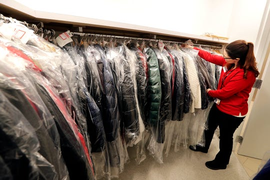 Denise Toomey, sales associate at Paradies Lagardere, checks coats in the storage area of the new airport coat check service.