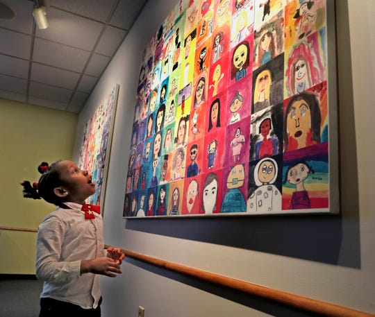 Jaila Grinnage-Brown, 5  looks at  the work of student artists at the Boys & Girls Club. The students  have created an art piece of self-portraits based on the art museum exhibit, Portraits of Milwaukee. The portraits were unveiled Wednesday, February 19, 2020.
