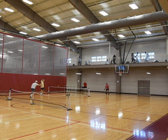 Four people play pickleball Wednesday morning at the Heber Springs Community Aquatics and Conference Center. Two more people walk laps around the building using the facility's elevated running/walking platform, while a seventh person works out on exercise equipment.