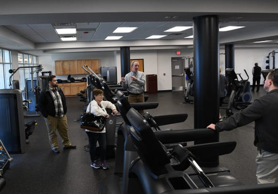 Batesville parks director Jeff Owens (standing on treadmill) talks to Mountain Home visitors Wednesday about the fitness center inside the Batesville Community Center and Aquatic Park. The fitness center is a major draw to the facility, Owens said.