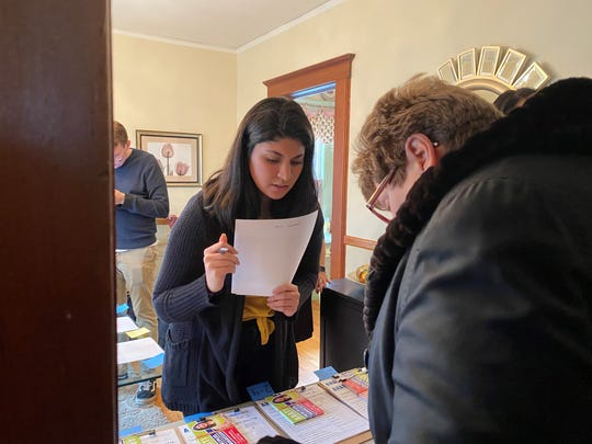 Reena Chojar helps a volunteer gather candidate information ahead of a canvass Sunday, Feb. 16, 2020.