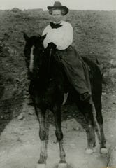 """On display as part of the Silver City Museum's """"Ranching in Grant County"""" exhibit, this 1909 photograph depicts a woman straddling a horse in an altered skirt, leading the July 4th parade in a scandalous-for-the-time stunt to raise awareness for women's suffrage."""