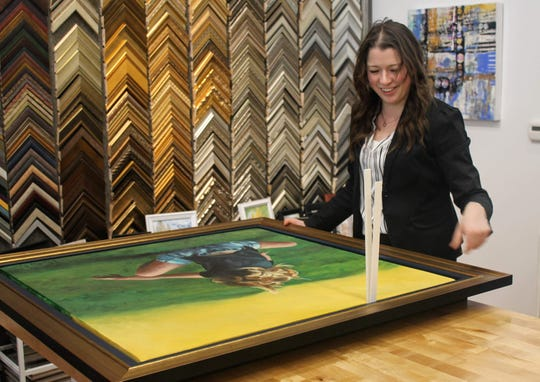 """Main Street Art owner Natalia Wohletz frames """"Tumble,"""" a piece of art she created using acrylic paint on canvas, in the new Main Street Art space."""