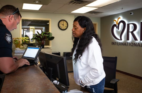 Behavioral health tecnician Ashanta Pleasant helps Peoria Police Department Officer Kevin Moe file paperwork for an involuntary admission on Feb. 20, 2020, at behavioral health center RI International in Peoria.