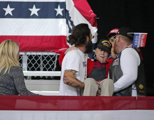 Jason Frank, left, and Larry Thorpe, right, carry World War II veteran Ervin Julian to his seat behind the podium at President Donald Trump's rally at Veterans Memorial Coliseum on Feb. 19, 2020, in Phoenix.