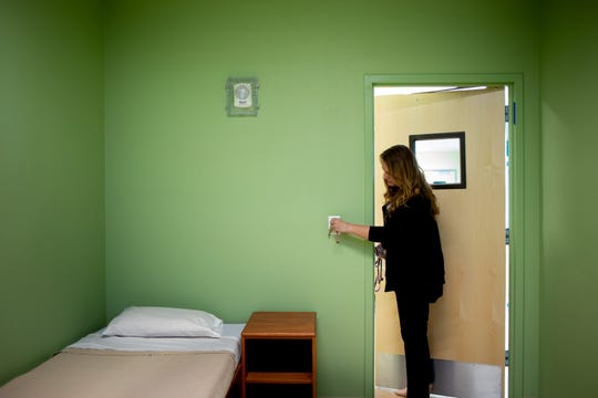 Site Director Teresa Hoffmeyer turns on the light in a guest room at RI International, a behavioral health center in Peoria, on Feb. 20, 2020.