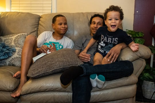 Alfred Stepp, center, sits with his sons Solomon, 11, left, and Seth, 3, in the living room of their home Monday, Feb. 17, 2020, in Port Huron.