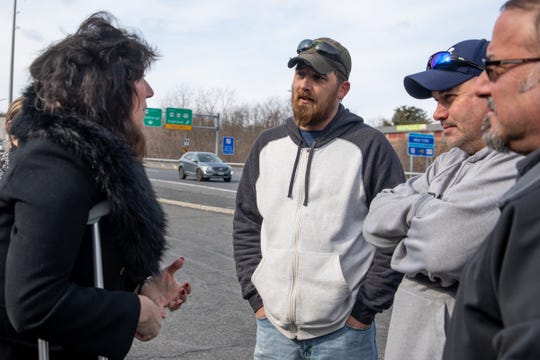 Sen. Sue Serino, left, talks to bridge workers Brad Gardner, center, and Jeff Smith, right after a rally in Highland on Thursday.