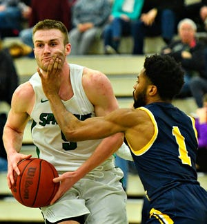 York College's Jared Wagner, left, works to get past St. Mary's Reggie Rouse during men's basketball action in Grumbacher Sport and Fitness Center at York College of Pennsylvania in Spring Garden Township, Wednesday, Feb. 19, 2020. Dawn J. Sagert photo