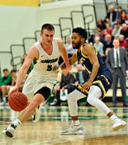 York College's Jared Wagner, left, advances the ball down the court while St. Mary's Reggie Rouse defends during men's basketball action in Grumbacher Sport and Fitness Center at York College of Pennsylvania in Spring Garden Township, Wednesday, Feb. 19, 2020. Dawn J. Sagert photo