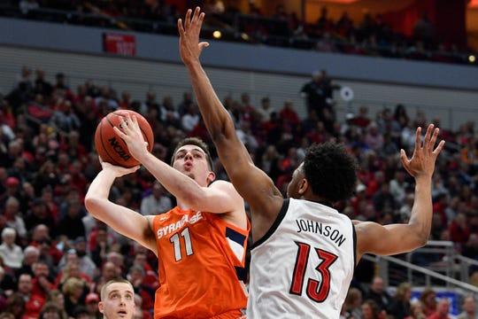 Syracuse Orange guard Joseph Girard III (11) shoots against Louisville Cardinals guard David Johnson (13) during the first half at KFC Yum! Center.