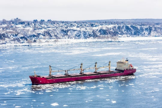 A cargo ship making its way through the ice-covered water surface of the Saint Lawrence River in Quebec, Canada.
