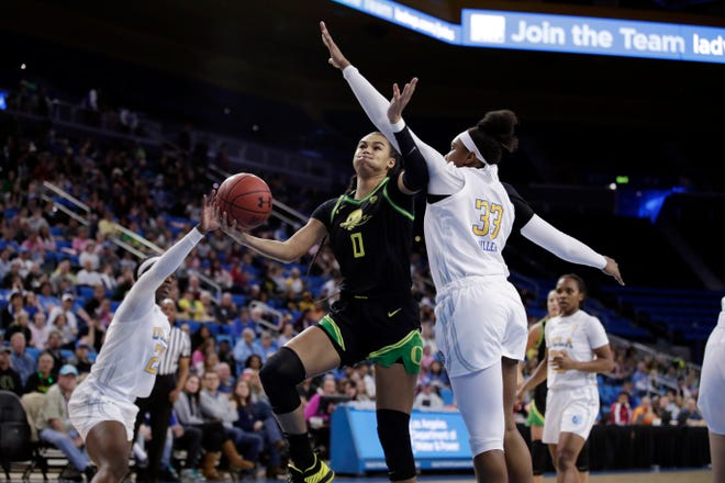 Oregon's Satou Sabally (0) shoots next to UCLA forward Lauryn Miller (33) during the first half of an NCAA college basketball game Friday, Feb. 14, 2020, in Los Angeles.