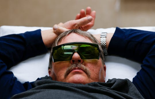 Ron Otradovec lies on a hospital bed while receiving Fractional CO2 Laser Therapy on his leg on Wednesday.