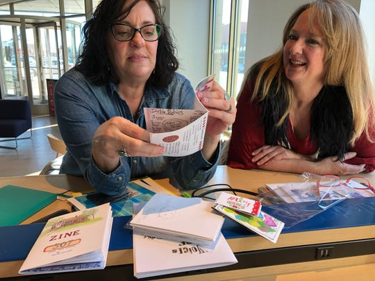 Kelley Holmes, left, flips thorugh a zine of recipes while Felicia Wilson looks on Wednesday, Feb. 19, 2020. The two organzied the St. Cloud Zine Fest along with Cheri Satre.