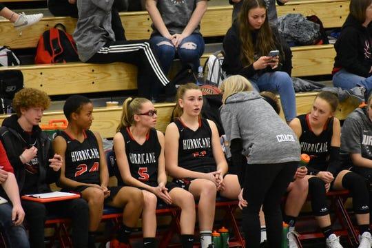 Hurricane coach Shelly Thomas (grey sweater) talks with players Sariya Sims (24), Brooke Thomas (11) and Kandalyn Hinton (center).