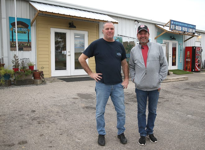 Store owners Mike O'Brien and Marc Rice stand for a photo on Feb. 17, 2020 at the Mexico Beach Market.