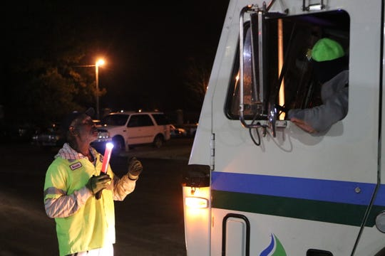 Waste Pro employees check safety gear on a garbage truck before the driver heads out on its route.