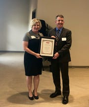 County Commission Chairwoman Susan Adams accepts a resolution designating Indian River County as a livable community from Jeff Johnson, director of AARP Florida.