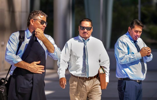 Lawyer Mark Fleming, left, walks with defendant Albert Lopez past defendant Bradley Campos outside the Lloyd George U.S. Courthouse Thursday, Feb. 6, 2020, following opening statements in a federal racketeering trial for eight Vagos Motorcycle Club members in Las Vegas.