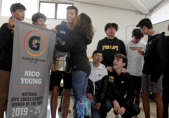Nico Young gets a hug and a kiss from his mother Lynne Young after being surprised at Newbury Park High on Thursday morning with his Gatorade Boys Cross Country Runner of the Year award.