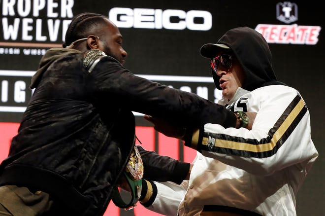 Deontay Wilder, left, shoves Tyson Fury during a face-off for photographers at a news conference Wednesday in Las Vegas for their heavyweight championship bout on Saturday.